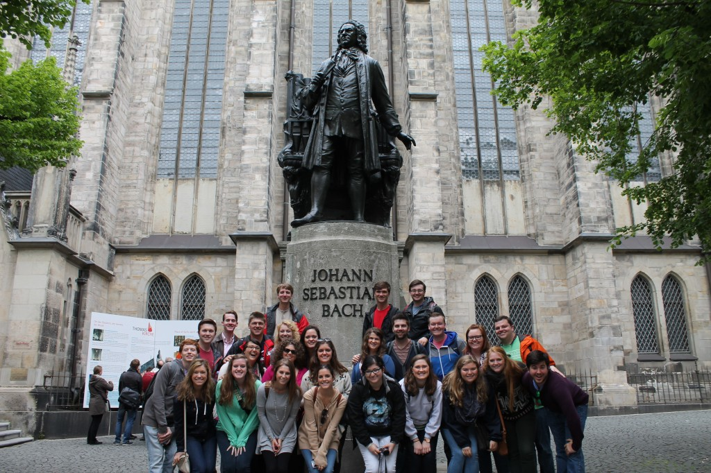 Concert Singers visit the Bach statue in Leipzig on their 2014 European tour.